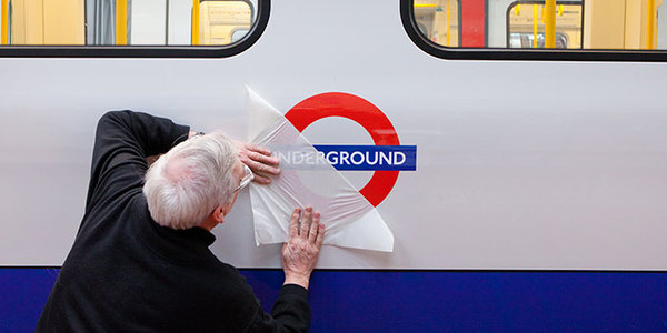 worker revealing underground sign on side of tube train