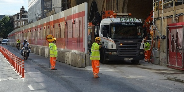 Construction workers directing a lorry out of a construction site whilst traffic is stopped