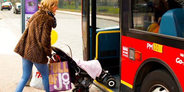 Woman boarding a bus with a buggy
